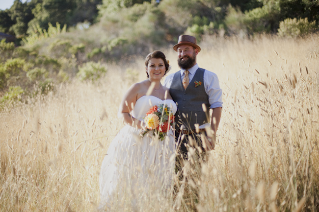 bride and groom pose in field of grass