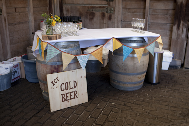 cold beer sign next to wine barrel drink table with pennants