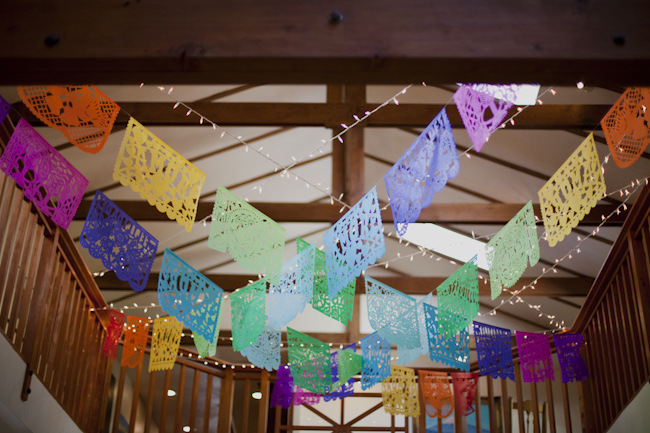colorful wedding pennants hanging from ceiling