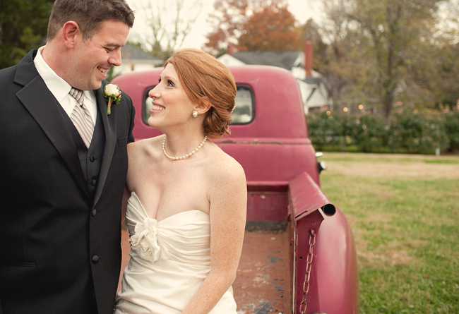 bride and groom sit on back of old red farm truck