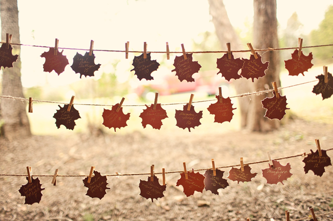 hand-written cut out leaves for table seating strung on twine with clothespins