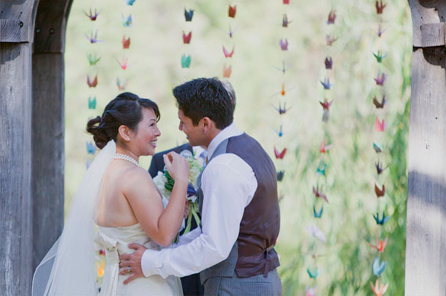 Bride and groom kiss in front of strands of color paper cranes at wedding ceremony