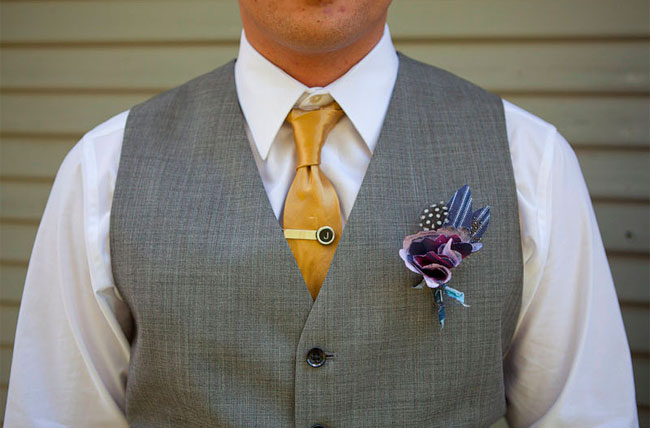Groom wearing gray vest and gold yellow tie with purple blue boutonniere