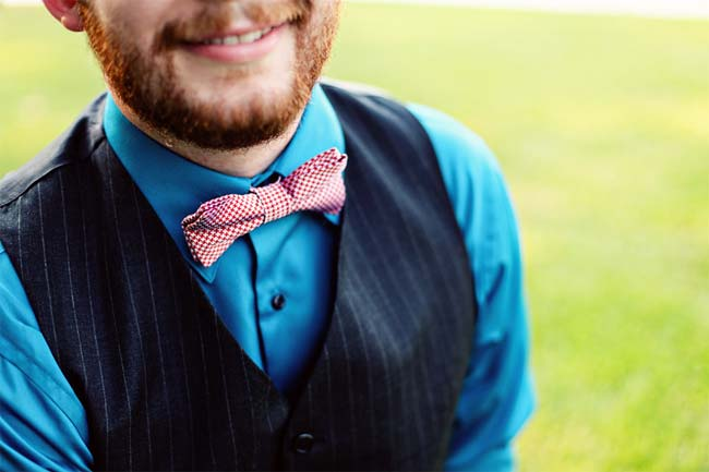 groom in red checkered bow-tie and navy vest