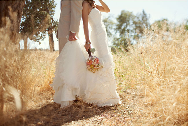 bride and groom stand back-to-back among field brush