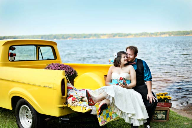 happy couple tail-gate in old yellow pickup truck