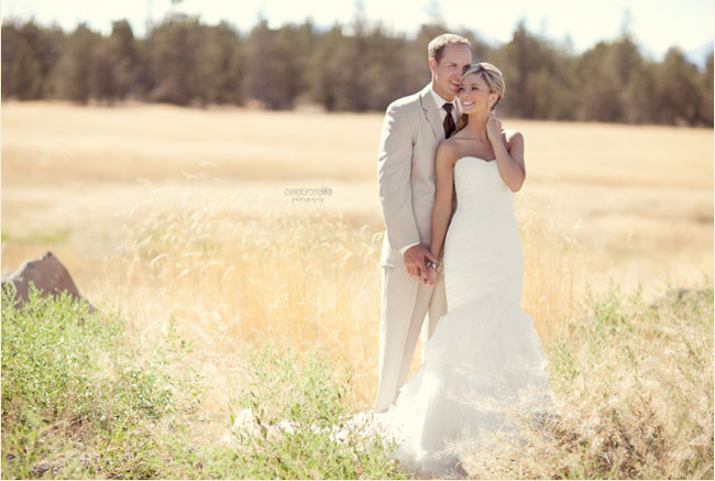 bride and groom stand in Oregon ranch field