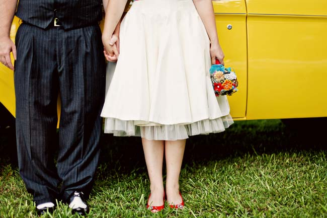 bride in red shoes; groom with his spats stand next to yellow car