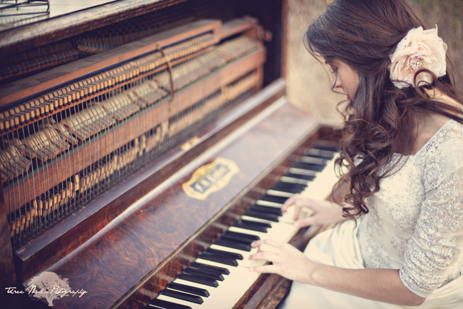bride with pink flower in hair plays old piano at engagement session
