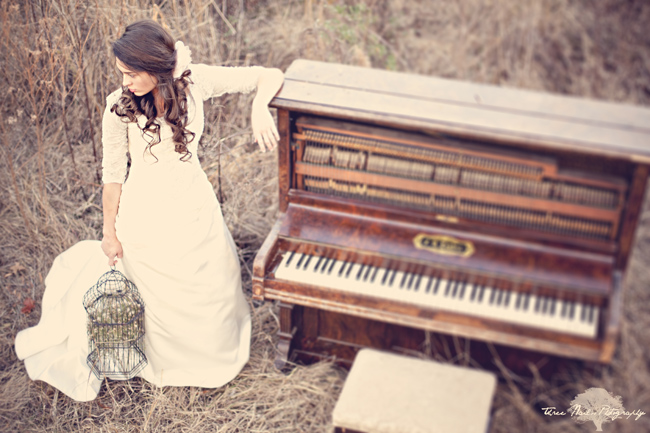 Bride leans against piano in the woods as she holds a vintage birdcage for engagement shoot