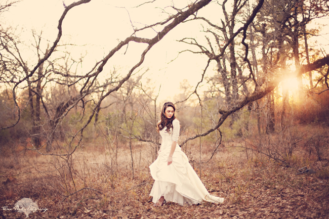Sun setting through tree branches with bride walking through fallen leaves in white dress at engagement session