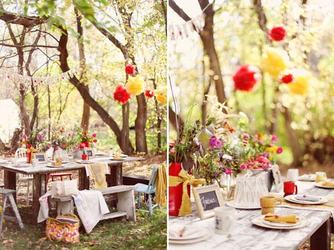 Old wooden table on grass outside with mismatched chairs and yellow burlap table runner, bunting and red and yellow paper pom poms hanging from the trees (left photo); close up view of same as left phototo)