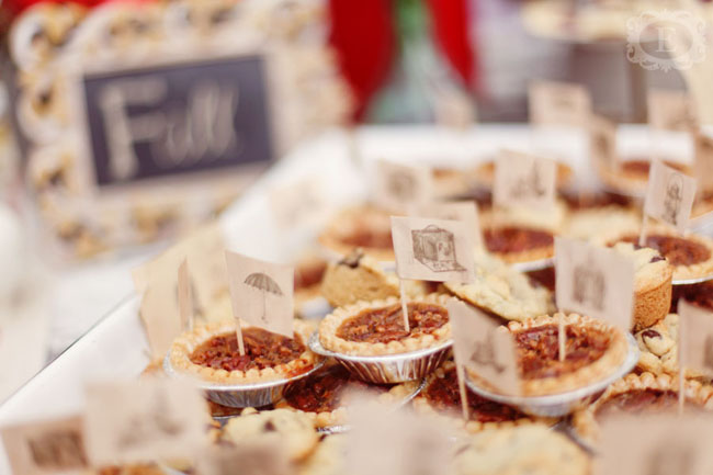 Mini pecan tarts with small tooth pick flags that have vintage images of a camera, umbrella and lantern on them
