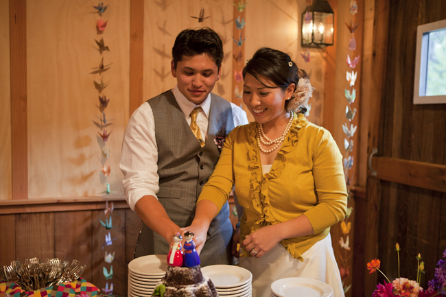 Bride and groom cut cake indoors with paper cranes hanging behind