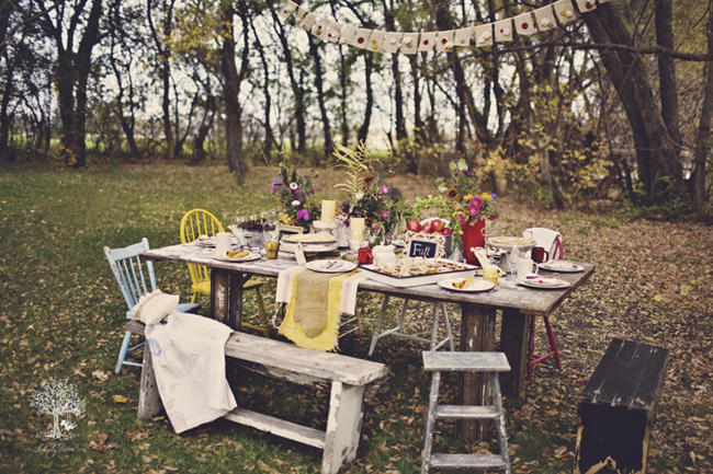 Old wooden table on grass outside with mismatched chairs and yellow burlap table runner, bunting hanging from the trees for outdoor picnic