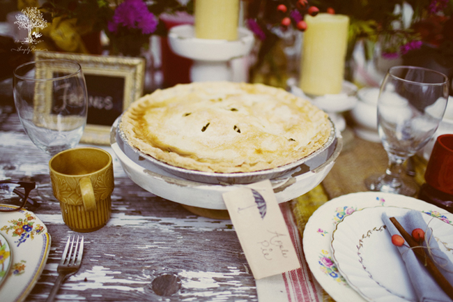 "Apple pie on an old wooden table for an outdoor picnic. Label attached with a picture of an umbrella and ""apple pie"""