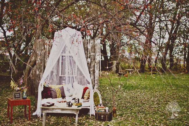 Outdoor picnic with bench with lots of throw pillow and draped sheer fabric hanging from tree  and other Flea Market and Antique Store Finds for Styled Shoot