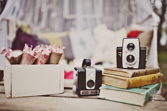 Vintage camera and books with a box full of smarties candies for outdoor picnic party