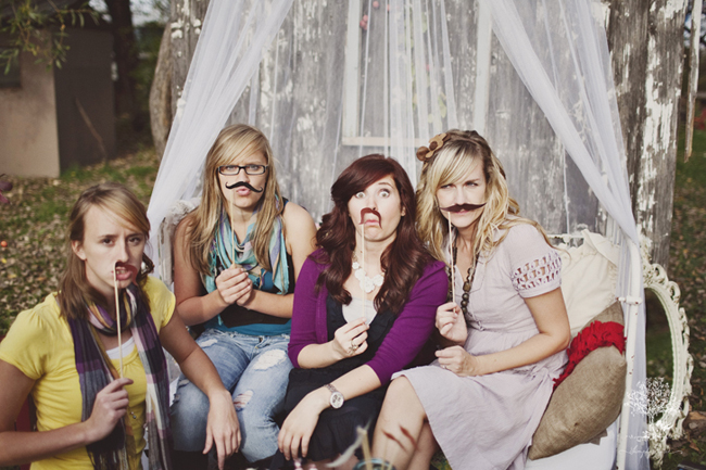 4 women sitting on bench with sheer fabric hanging from tree for outdoor picnic posing with mustaches on a stick