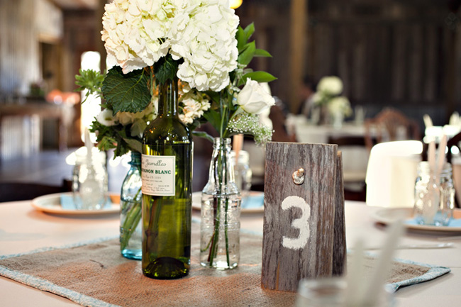 Centerpiece With Recycled Bottles And Rustic Wood Table Numbers