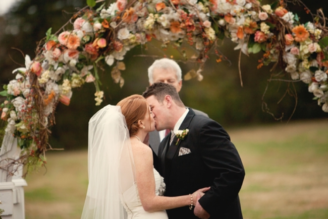 spectacular arch filled with white, peach, and pink flowers over bride and groom
