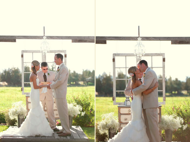 bride and groom kiss on wood stage at Oregon ranch wedding ceremony