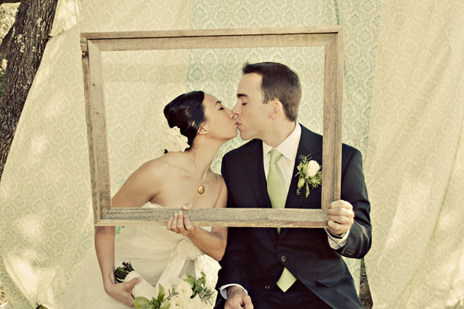 bride and groom kiss while holding empty wood picture frame