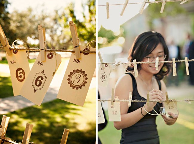 escort cards with table numbers stamped onto paper luggage tags hanging from clothespins