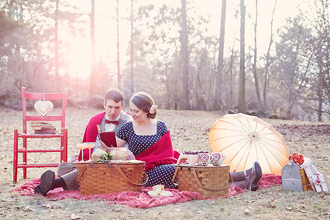 Sun setting on bread and butter inspiration shoot. Bride and groom sit on picnic blanket reading to each other with parasol, red chair, and baskets surrounding them