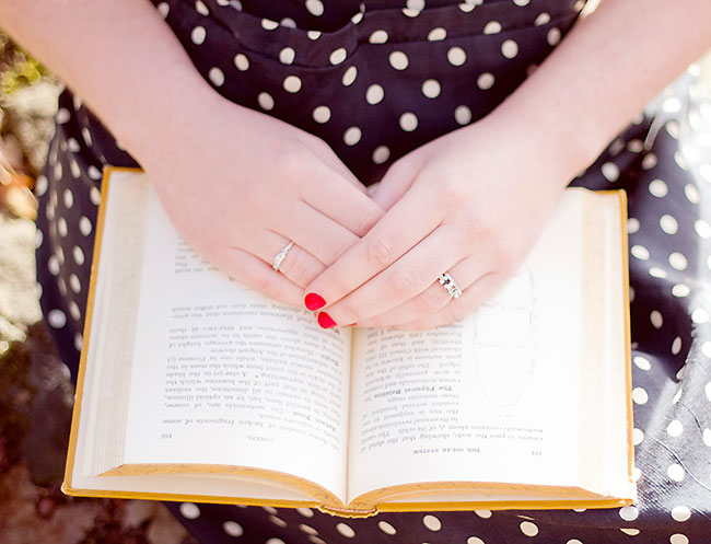 Engagement shoot bride with red nailpolish folds hands on old book in her lap