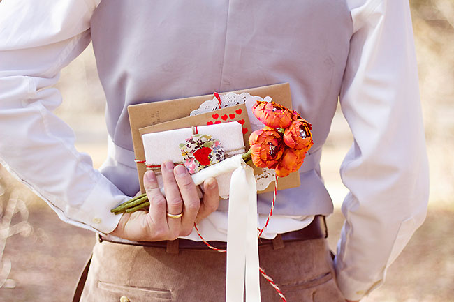 Engagement shoot groom holds cards and Emici Bridal bouquet behind his back