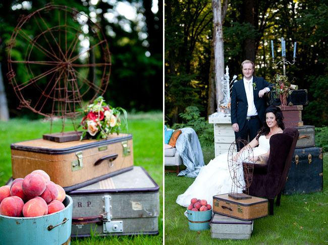 Wedding reception at private estate: Basket of peaches beside vintage suitcases on grass with bride sitting on chair and groom standing beside.