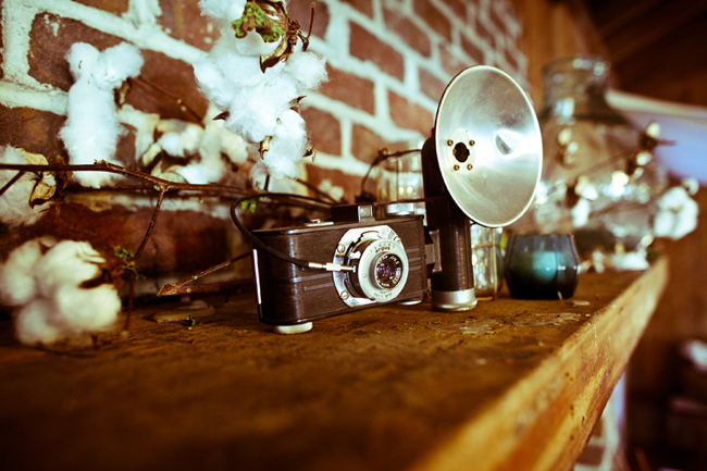 vintage camera with cotton branch on wood mantle with red brick
