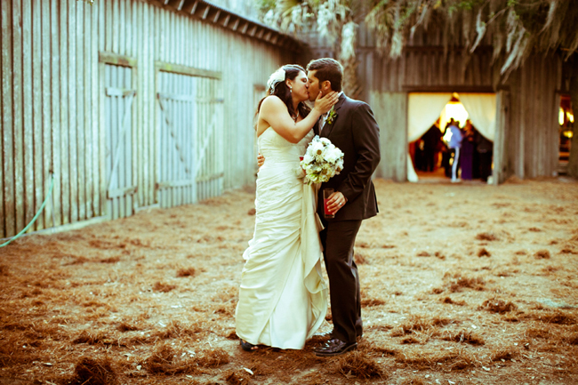 bride and groom kiss standing on hay floor near barn