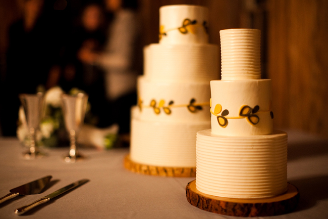 Small 3-tier white cake and 4-tier cake with yellow flower design on wood rounds