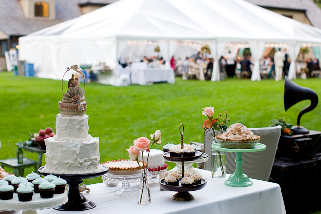 Carnival inspired wedding dessert table with cupcakes, wedding cake, and pies in foreground; giant canopy tent in background