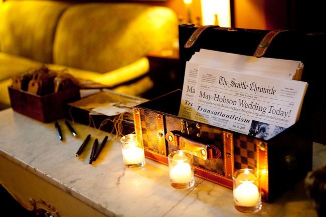"The Ruins in Seattle: Wedding programs that are mini ""Seattle Chronicle Newspapers"" inside a trunk with candles burning in front"
