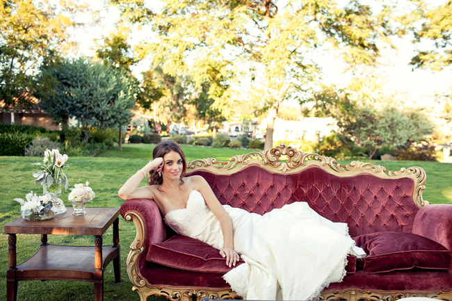 bride laying on outdoor vintage red couch at Inn at Rancho Santa Fe