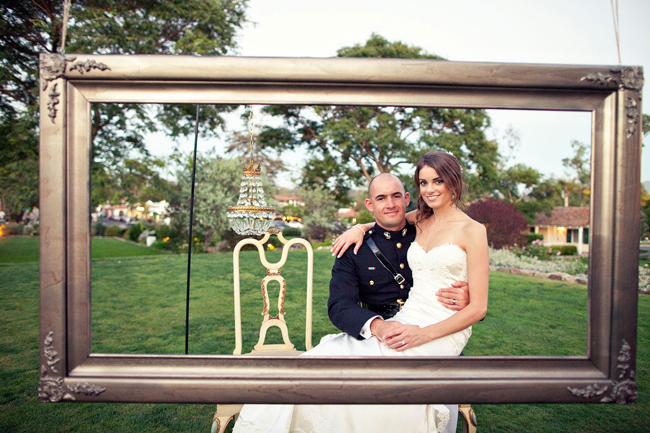 Bride And Groom Sit Outdoors At Large Frame Photo Booth For Wedding Picture