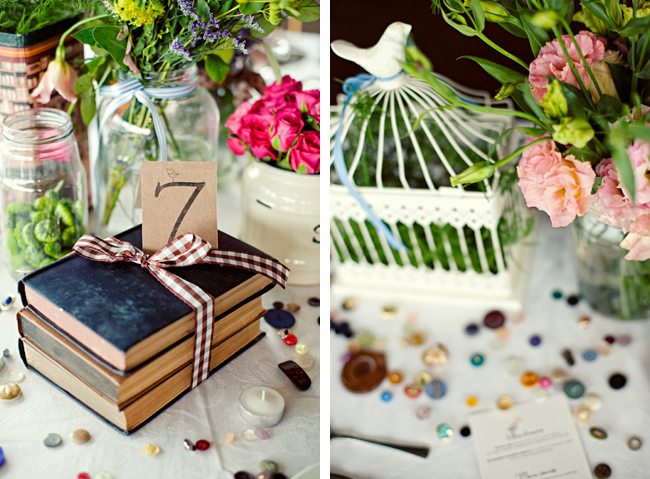Vintage books tied up with ribbon, birdcages, mason jars, and tea tins with colorful flowers at Red Ivory Lodge wedding in South Africa