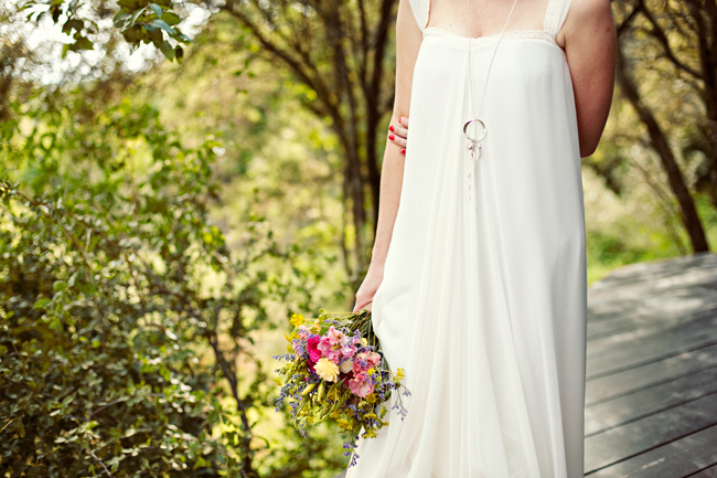 bride holding flower bouquet walks along porch at  Red Ivory Lodge in South Africa