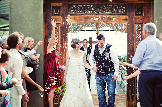 Throwing confetti on bride and groom as they walk under door from wedding ceremony at Red Ivory Lodge wedding in South Africa