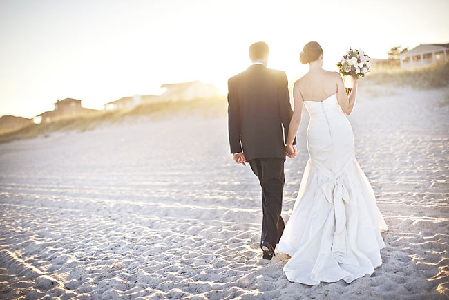 newlyweds walk on sand beach near Carolina Yacht Club