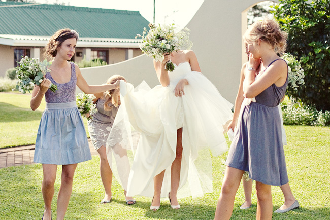 Bride hides her face as her dress is lifted up by bridesmaids