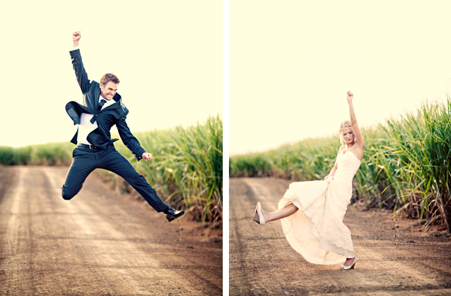 bride and groom jump on dirt road in sugar cane farm field