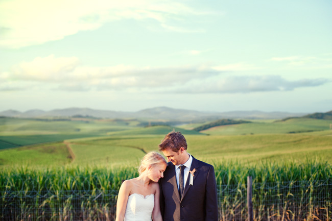 bride and groom stand together in front of sugar cane field background