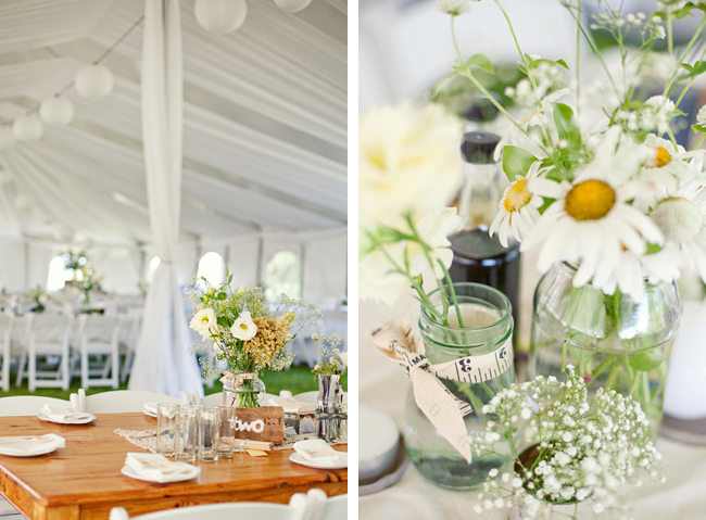 White canopy tent with drapery and lanterns above, white daisy flowers as centerpieces