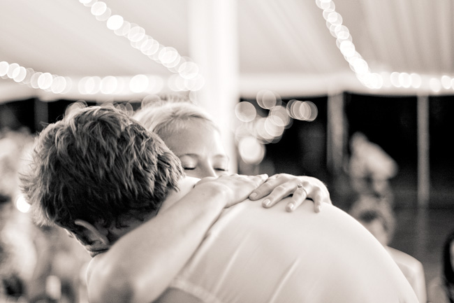 black and white photo of bride and groom hugging at wedding reception