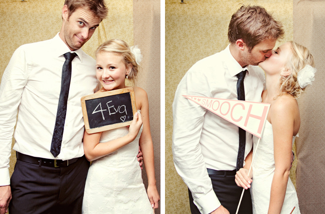 bride and groom in the photo booth holding a penant that says Smooch