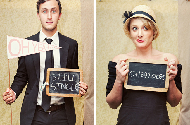 Guests in black attire holding a pennant and chalkboard sign in the photobooth